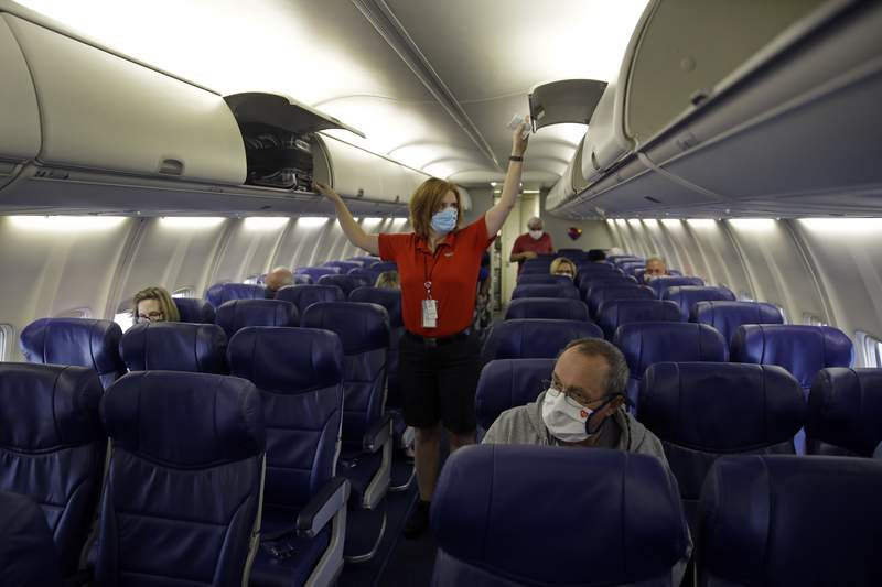 FILE - In this May 24, 2020, file photo, a Southwest Airlines flight attendant prepares a plane bound for Orlando, Fla. for takeoff at Kansas City International airport in Kansas City, Mo. About 40,000 workers in the airline industry are facing layoffs on Thursday, Oct. 1, unless Congress comes up with another aid package. (AP Photo/Charlie Riedel, File)