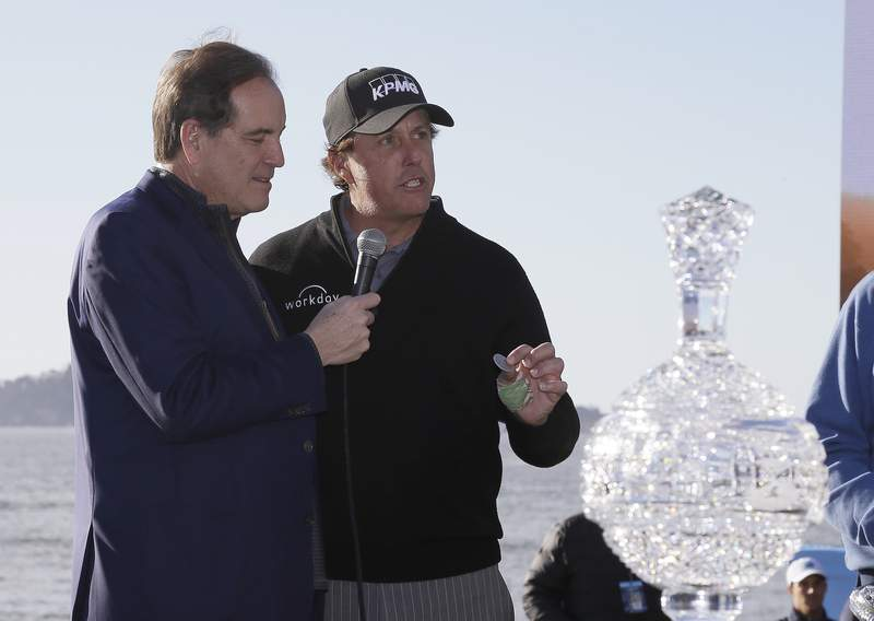 FILE - In this Monday, Feb. 11, 2019, file photo, while being interviewed by broadcaster Jim Nantz, left, Phil Mickelson holds up a silver dollar that belonged to his grandfather during an awards ceremony on the 18th green of the Pebble Beach Golf Links after winning the AT&T Pebble Beach Pro-Am golf tournament, in Pebble Beach, Calif. Nantz has worked the Final Four and Masters for the last 34 years and is missing them in 2020 because of the new coronavirus pandemic. (AP Photo/Eric Risberg, File)