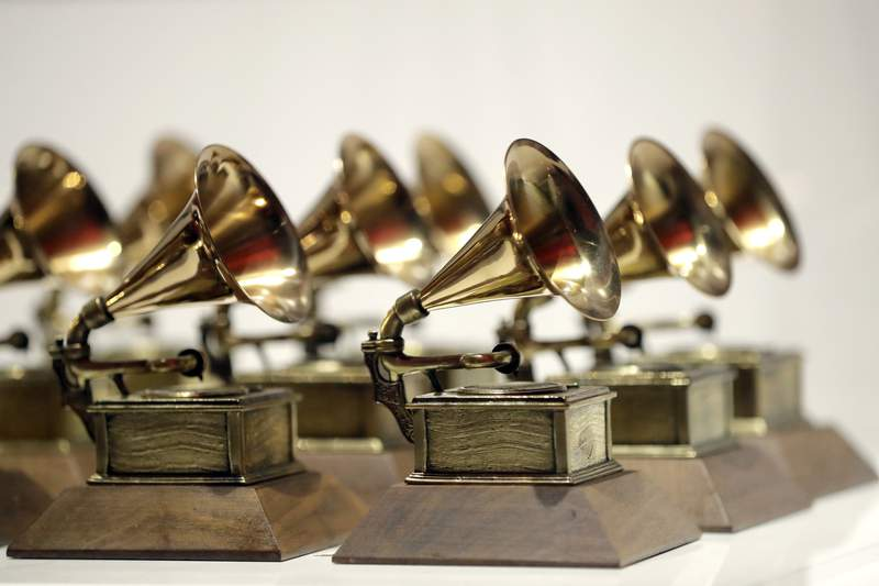 FILE - In this Oct. 10, 2017, file photo, various Grammy Awards are displayed at the Grammy Museum Experience at Prudential Center in Newark, N.J. The Grammy Museum will reopen next month after being closed for more than a year due to the coronavirus pandemic. The museum in downtown Los Angeles announced Tuesday that it will be open to the public on May 21. (AP Photo/Julio Cortez, File)