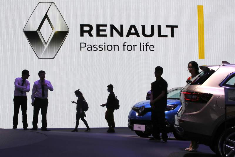 FILE - In this April 20, 2017, file photo, visitors walk past the Renault stand during the Auto Shanghai 2017 show in Shanghai, China. Renault SA said Tuesday, April 14, 2020, it will shut down its main China business and focus on electric and commercial vehicles. (AP Photo/Ng Han Guan, File)