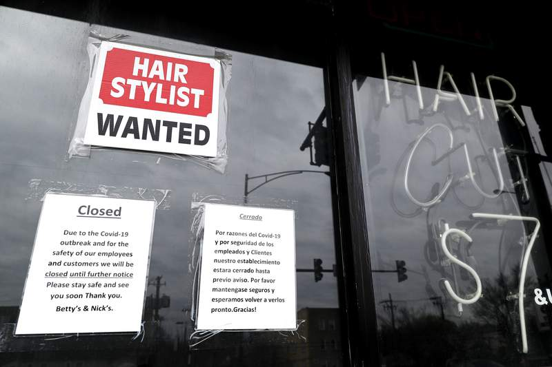 FILE - In this April 30 ,2020 file photo, a barber shop shows closed and hiring sign during the COVID-19 in Chicago.  On Thursday, Aug. 27, just over 1 million Americans applied for unemployment benefits last week, a sign that the coronavirus outbreak continues to threaten jobs even as the housing market, auto sales and other segments of the economy rebound from a springtime collapse. (AP Photo/Nam Y. Huh, File)