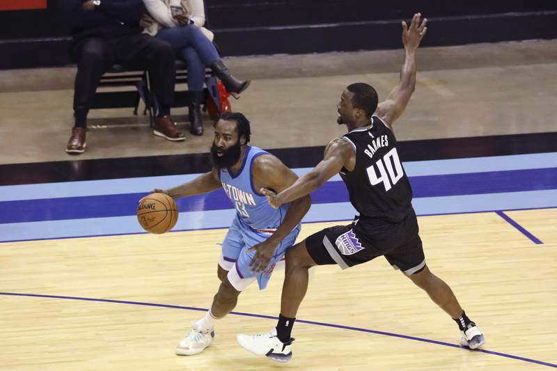 Sacramento Kings Harrison Barnes gets a hand on Houston Rockets guard James Harden during the second half of an NBA basketball game Thursday Dec. 31, 2020, in Houston. (AP Photo/Richard Carson)