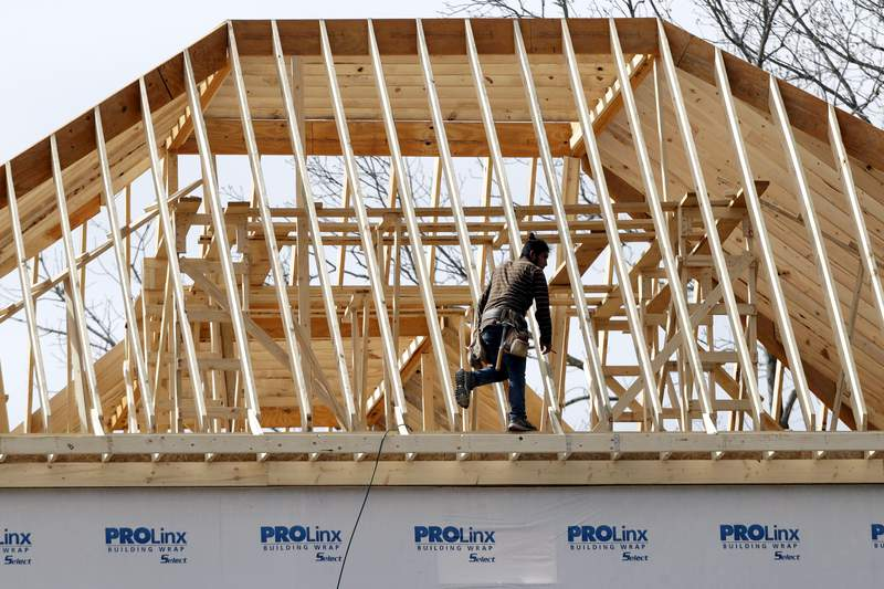 In this March 25, 2020, photo, a construction worker walks along a roof on a new home in Nashville, Tenn.  US home construction rebounded 4.3% in May after steep declines caused by shutdowns due to the coronavirus. The Commerce Department reported Wednesday, June 17,  that new homes were started at a seasonally adjusted annual rate of 974,000 last month after steep declines in April and March.(AP Photo/Mark Humphrey)
