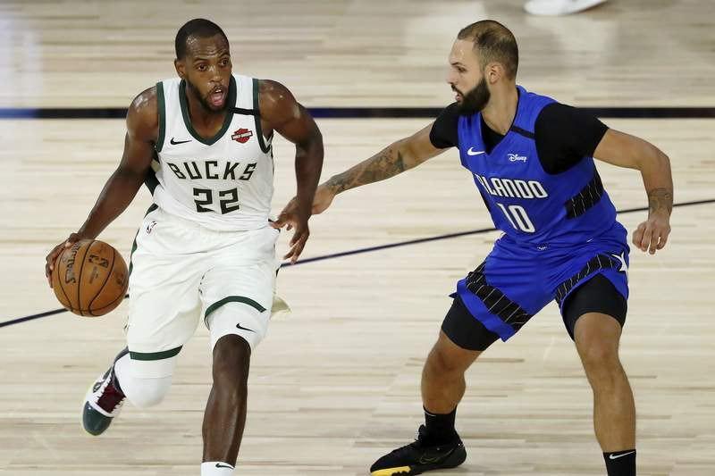 Milwaukee Bucks forward Khris Middleton (22) dribbles while defended by Orlando Magic guard Evan Fournier (10) during the first half of Game 1 of an NBA basketball first-round playoff series, Tuesday, Aug. 18, 2020, in Lake Buena Vista, Fla. (Kim Klement/Pool Photo via AP)