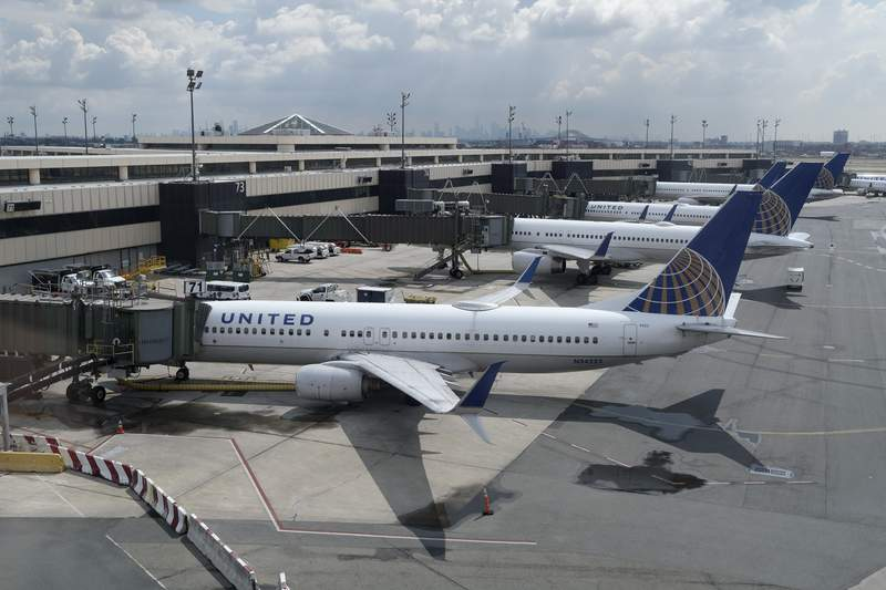 FILE - In this Wednesday, July 1, 2020 file photo, United Airlines planes are parked at gates at Newark Liberty International Airport in Newark, N.J. A nonprofit software developer is testing a smartphone app and data framework that could make it easier for international airline passengers to securely show they've complied with COVID-19 testing requirements. It's an attempt to help get people back to flying after the pandemic sent global air travel down by 92%. The Switzerland-based Commons Project Foundation was conducting a test Wednesday, Oct 21 of its CommonPass digital health pass on United Airlines Flight 15 from London's Heathrow to Newark Liberty International Airport, using volunteers carrying the app on their smartphones. (AP Photo/Seth Wenig, file)