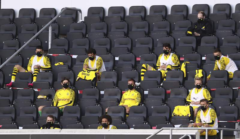 FILE - In this Sunday, May 31, 2020, substitutes for Borussia Dortmund, wearing face masks to protect against coronavirus, look on from the stands during the German Bundesliga soccer match between SC Paderborn 07 and Borussia Dortmund at Benteler Arena in Paderborn, Germany. The German Bundesliga will keep five substitutions for the 2020-21 season because of the coronavirus pandemic. The 36 clubs in the top two German mens soccer leagues voted at a German Football League meeting Thursday, Sept. 3, 2020 to continue the rule for next season. (Lars Baron/Pool via AP, file)
