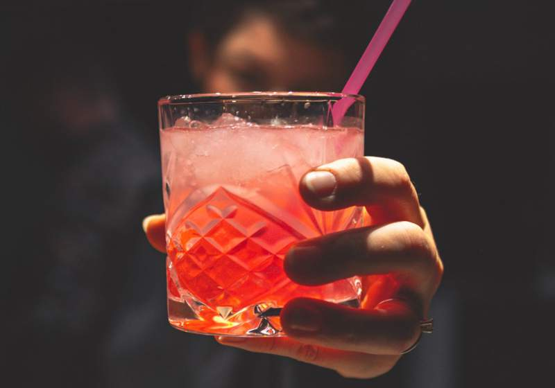 A person holds an alcoholic beverage.