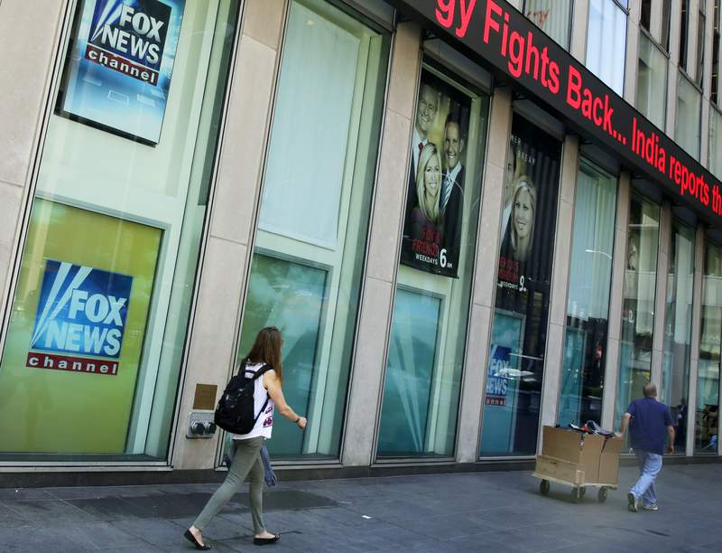 FILE- In this Aug. 1, 2017 file photo, people pass the News Corporation headquarters building and Fox News studios in New York. The parents of slain Democratic National Committee employee Seth Rich have reached a settlement of their lawsuit that alleged Fox News exploited their son's death in stories and commentary. Both sides confirmed the settlement on Tuesday, Nov. 24, 2020. (AP Photo/Richard Drew, File)