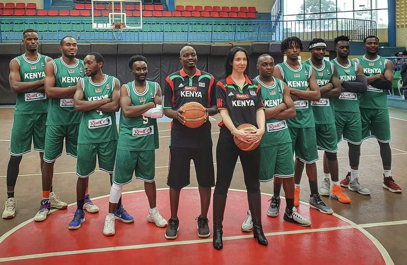 Kenya national men's basketball team head coach Liz Mills, center-right, poses with assistant coach Sadat Gaya, center-left, for a photograph with the team at Nyayo Stadium in Nairobi, Kenya Saturday, Feb. 13, 2021. Australian Liz Mills has been coaching men's basketball teams for 10 years in Africa and is now head coach of Kenya and the only woman in the world currently in charge of a men's national basketball team. (Courtesy of Liz Mills)