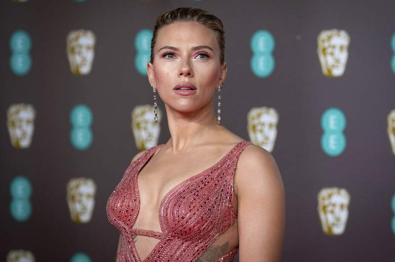 """FILE - Scarlett Johansson arrives at the Bafta Film Awards, in central London, Feb. 2 2020. Johansson is suing the Walt Disney Co. over the companys streaming release of """"Black Widow,"""" which she said breached her contract and deprived her of potential earnings. The Black Widow star and executive producer filed a suit Thursday, July 29, 2021, in the Los Angeles Superior Court that said her contract guaranteed an exclusive theatrical release. (Photo by Vianney Le Caer/Invision/AP, File)"""