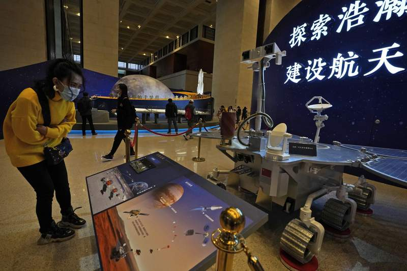 "A visitor to an exhibition looks at a display with a replica of the Chinese Mars Rover of the Tianwen-1 spacecraft in Beijing on March 12, 2021. China's National Space Agency confirmed Wednesday, March 31, 2021 that it had working-level meetings and communications with NASA from January to March to ensure the flight safety"" of their crafts. (AP Photo/Ng Han Guan)"