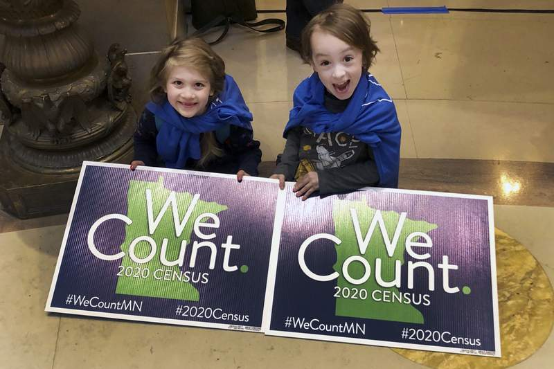 FILE - In this April 1, 2019 file photo, Noelle Fries, 6, left, and Galen Biel, 6, both of Minneapolis, attend a rally at the Minnesota Capitol to kick off a year-long drive to try to ensure that all Minnesota residents are counted in the 2020 census. Minnesotans spent 18 months worrying over whether the 2020 Census would finally cost them a precious seat in Congress. Residents voluntarily returned their census forms at the highest rate in the nation. Their dedication likely saved the day. (AP Photo/Steve Karnowski, File)