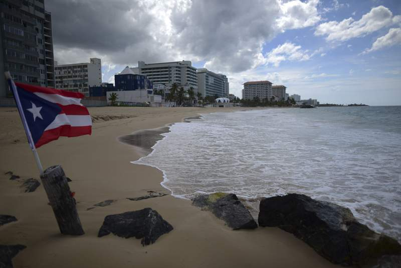 ARCHIVO - En esta foto de archivo del 21 de mayo de 2020, la bandera de Puerto Rico ondea en una playa desierta en Ocean Park, San Juan, Puerto Rico. (AP Foto/Carlos Giusti, File) PUERTO RICO OUT-NO PUBLICAR EN PUERTO RICO