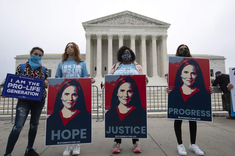 Supporters for the confirmation of President Donald Trump's Supreme Court nominee Amy Coney Barrett, rally at the Supreme Court on Capitol Hill in Washington, Tuesday, Oct. 13, 2020. (AP Photo/Jose Luis Magana)