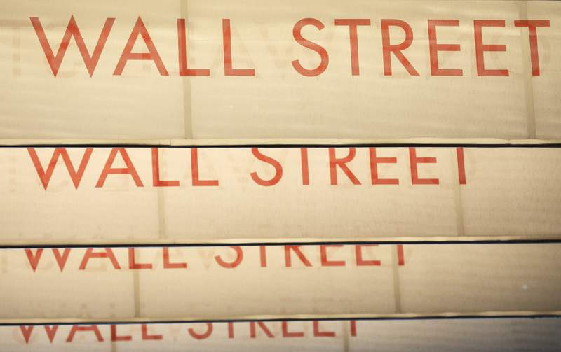 FILE - In this July 30, 2020 file photo, signs for Wall Street are shown, in New York. Wall Street is drifting Wednesday morning, Aug. 19 as even a record high for the S&P 500 fails to jolt much life into the market. The S&P 500 was edging up by 0.1% after the first half hour of trading, a day after it wiped out the last of its losses created by the pandemic and surpassed its Feb. 19 peak. (AP Photo/Mark Lennihan, File)