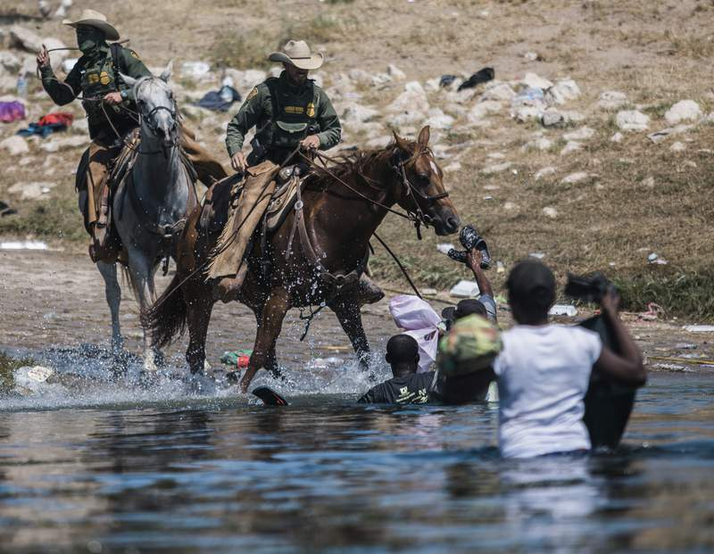 U.S. Customs and Border Protection mounted officers attempt to contain migrants as they cross the Rio Grande from Ciudad Acua, Mexico, into Del Rio, Texas, Sunday, Sept. 19, 2021. Thousands of Haitian migrants have been arriving to Del Rio, Texas, as authorities attempt to close the border to stop the flow of migrants. (AP Photo/Felix Marquez)
