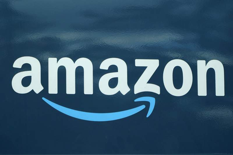 An Amazon logo appears on an Amazon delivery van, Thursday, Oct. 1, 2020, in Boston.  Amazon said Tuesday, Jan. 5, 2021,  that it bought 11 jets from Delta and WestJet airlines to boost its growing delivery network and get orders to shoppers faster. The company said its the first time it purchased planes for its delivery network.   (AP Photo/Steven Senne)
