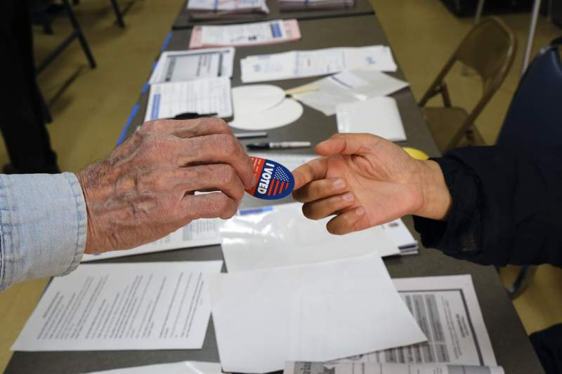 Early voter receives his I-Voted sticker, at an early voting polling station at the Ranchito Avenue Elementary School in the Panorama City section of Los Angeles on Monday, March 2, 2020. Major changes to the way people vote has election advocates on edge as Californians cast ballots in the Democratic presidential contest and other primary races. (AP Photo/Richard Vogel)
