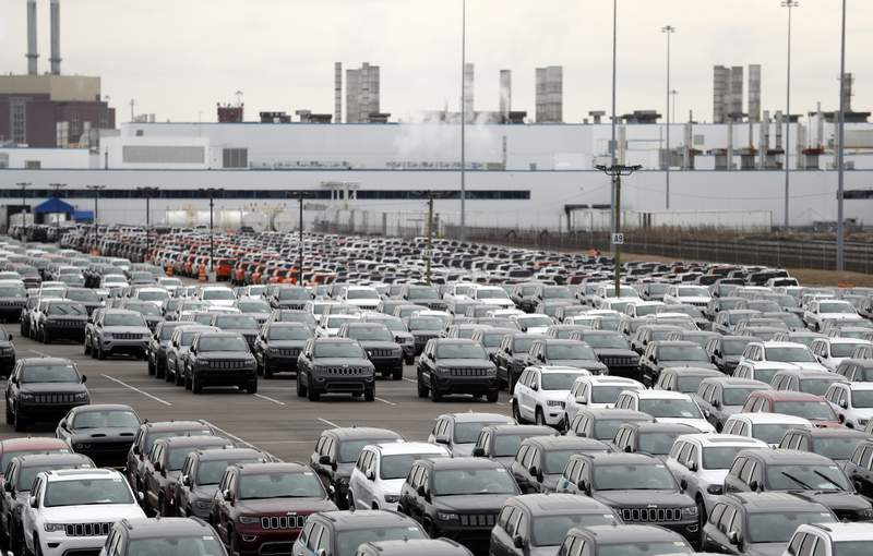 FILE - In this Feb. 26, 2019, file photo, Jeep vehicles are parked outside the Jefferson North Assembly Plant in Detroit. Fiat Chrysler is backing off a planned May 4 restart at its North American factories because some U.S. states still will have stay-home orders in place. The move likely means that factories of all three Detroit automakers will be idled for at least another two weeks as they negotiate reopening terms with the United Auto Workers union. (AP Photo/Carlos Osorio, File)