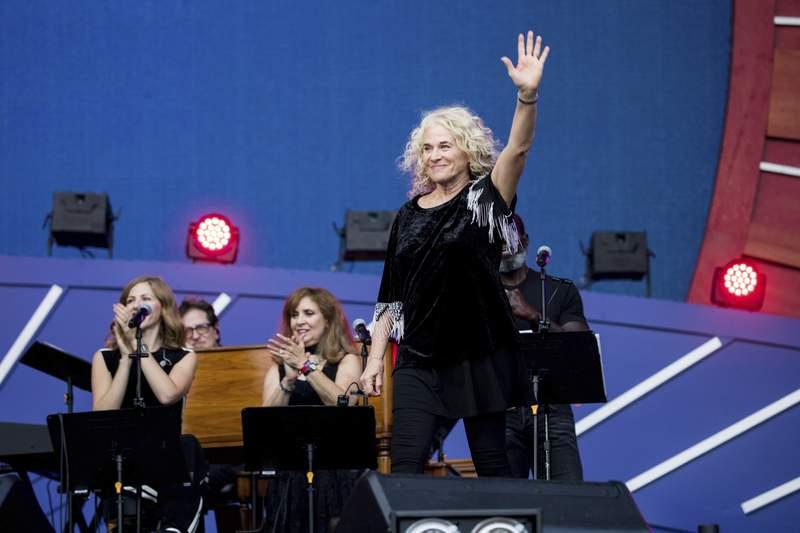 FILE - In this Sept. 28, 2019, file photo, Carole King waves to the crowd as she takes the stage at the 2019 Global Citizen Festival in New York. Poised over the piano, King was set to play I Feel the Earth Move during a recent virtual fundraiser for Joe Biden when the Democratic presidential nominee himself beat her to it. On my playlist, Carole! Biden proclaimed, holding up his phone and letting a few seconds of the song blast.(AP Photo/Julius Constantine Motal, File)