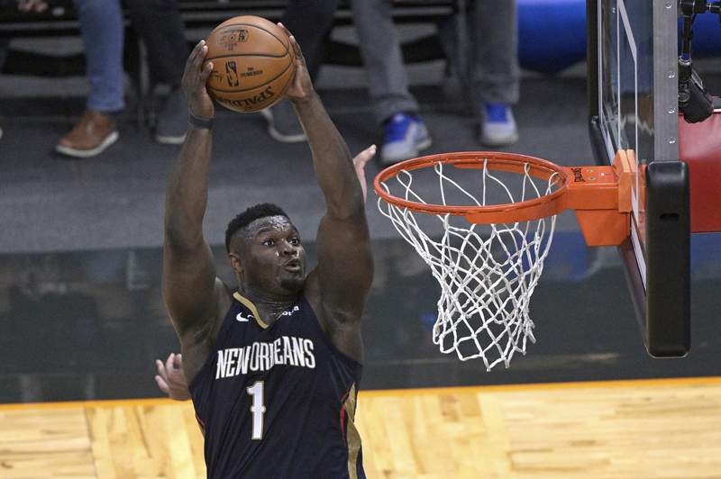 New Orleans Pelicans forward Zion Williamson (1) dunks after gettin an alley-oop pass during the first half of the team's NBA basketball game against the Orlando Magic, Thursday, April 22, 2021, in Orlando, Fla. (AP Photo/Phelan M. Ebenhack)