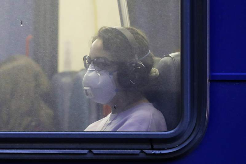In this March 6, 2020 photo, a woman wears a mask as she rides a bus in downtown Seattle during an evening commute. Expressing alarm both about mounting infections and slow government responses, the World Health Organization declared Wednesday that the global COVID-19 coronavirus crisis is now a pandemic but also said it's not too late for countries to act. (AP Photo/Ted S. Warren)