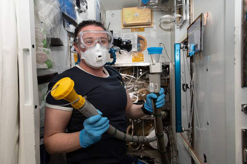 File photo: NASA astronaut Serena Auñón-Chancellor performs plumbing duties inside the International Space Station's toilet, also known as the Waste and Hygiene Compartment, located in the U.S. Tranquility module. (Image: NASA)