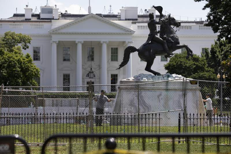The base of the statue of former president Andrew Jackson is power washed inside a newly closed Lafayette Park, Wednesday, June 24, 2020, in Washington, which has been the site of protests over the death of George Floyd, a black man who was in police custody in Minneapolis. Floyd died after being restrained by Minneapolis police officers. (AP Photo/Jacquelyn Martin)