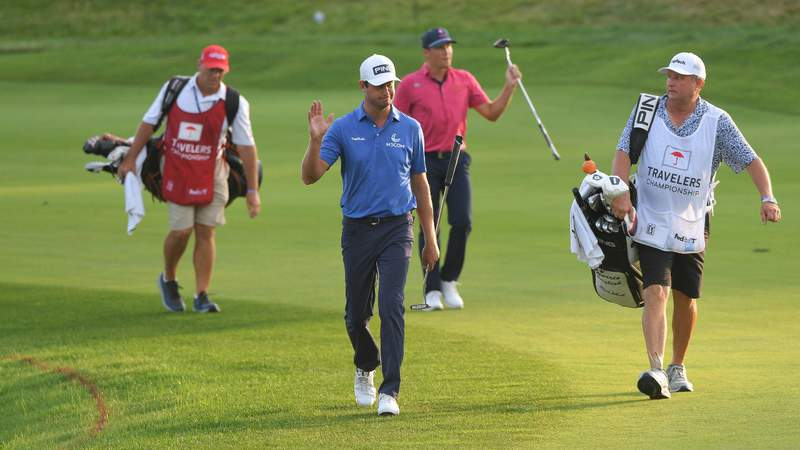 Harris English and Kramer Hickok wave to fans while walking towards the 17th green during the fifth playoff hole during the final round of the Travelers Championship. Photo by Ben Jared/PGA TOUR