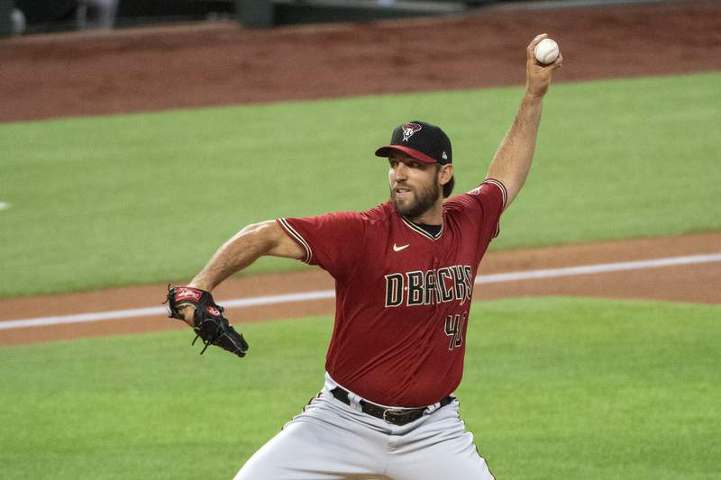 FILE - Arizona Diamondbacks Madison Bumgarner throws against the Texas Rangers during the first inning of a baseball game in Arlington, Texas, in this Wednesday, July 29, 2020, file photo. Diamondbacks manager Torey Lovullo enters his fifth year with the Diamondbacks   and the final year of his current contract  under a substantial amount of scrutiny. The Diamondbacks are hoping left-hander Madison Bumgarner can turn into the top-of-the-rotation starter they wanted him to be when he signed an $85 million, five-year deal before last season. (AP Photo/Jeffrey McWhorter, File)