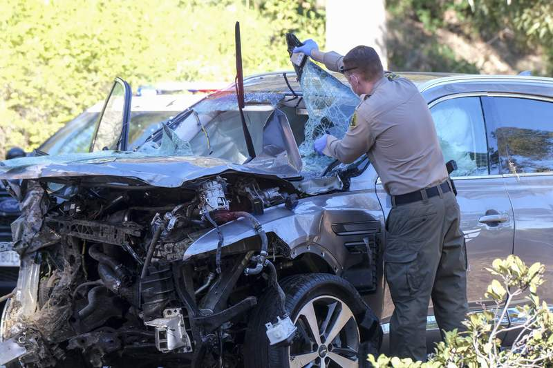 FILE - In this Feb. 23, 2021, file photo, a law enforcement officer looks over a damaged vehicle following a rollover accident involving golfer Tiger Woods in the Rancho Palos Verdes suburb of Los Angeles. A man who found Woods unconscious in a mangled SUV last week after the golf star who later told sheriff's deputies he did not know how the collision occurred and didn't even remember driving, crashed the vehicle in Southern California, authorities said in court documents. Law enforcement has not previously disclosed that Woods had been unconscious following the collision. (AP Photo/Ringo H.W. Chiu,File)