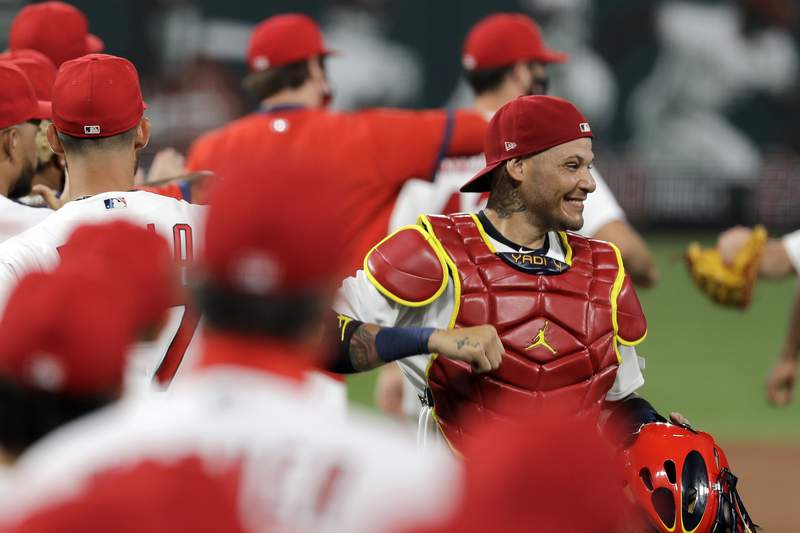 FILE - In this Friday, July 24, 2020, file photo, St. Louis Cardinals catcher Yadier Molina, right, celebrates a 5-4 win over the Pittsburgh Pirates in a baseball game in St. Louis.  Molina says hes one of the players on his team who has tested positive for the coronavirus. The nine-time All-Star revealed his diagnosis Tuesday, Aug. 4, 2020, in a Spanish-language Instagram post. (AP Photo/Jeff Roberson, File)