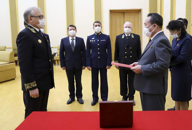 In this photo released by Russian Embassy in the DPRK/Russian Foreign Ministry Press Service on Tuesday, May 5, 2020, Russian Ambassador to Democratic People's Republic of Korea Alexander Matsegora, left, and Democratic People's Republic of Korea Foreign Minister Ri Son-gwon, foreground right, both wearing face masks to protect against coronavirus, attend a ceremony of awarding North Korean leader Kim Jong-un with Russia's 75th anniversary Victory medal for his major contribution in commemorating Soviet soldiers, who died in 1945 during Korea's liberation, at the Mansudae Palace of Congress in Pyongyang, North Korea. Russian President Vladimir Putin has awarded Kim Jong Un a commemorative war medal marking the 75th anniversary of the victory over Nazi Germany. (Russian Embassy in the DPRK/Russian Foreign Ministry Press Service via AP)