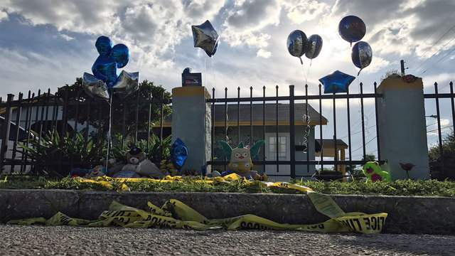 Crime scene tape, balloons and stuffed animals line the street in front of Little Miracles Academy in Orlando, Fla. on Tuesday, Aug. 8, 2017, one day after 3-year-old Myles Hill was found dead in a day care van.