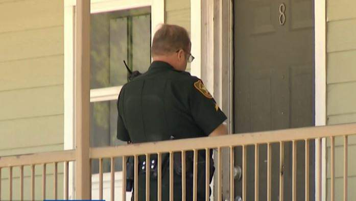 A Marion County sheriff's deputy prepares to post an eviction notice on an apartment door.