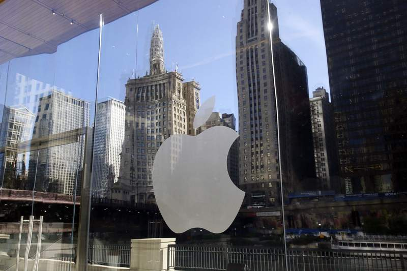 FILE - In this Thursday, Oct. 19, 2017, file photo, buildings are reflected behind the logo at an Apple Store in downtown Chicago. Apple Music is coming to a city near you  the streaming service launched daily music charts focused on particular cities around the world on Monday, April 26, 2021. (AP Photo/Kiichiro Sato, File)