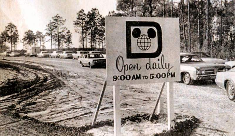 A line of cars heading down a barely paved road (Motor Inn Plaza) leading to The Walt Disney World Preview Center in 1970