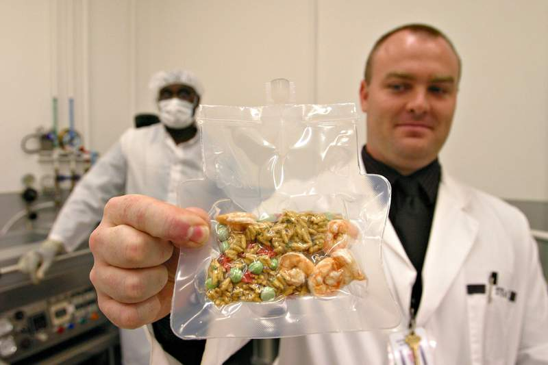 Food Technician Al Russ, left, and Food Scientist Steve French, right, show a finished packet of freeze-dried shrimp fried rice in NASA's Space Food Systems Laboratory at Johnson Space Center in Houston, Wednesday, Nov. 19, 2003. The lab is where the American half of the food for the International Space Station is prepared. (AP Photo/Michael Stravato)