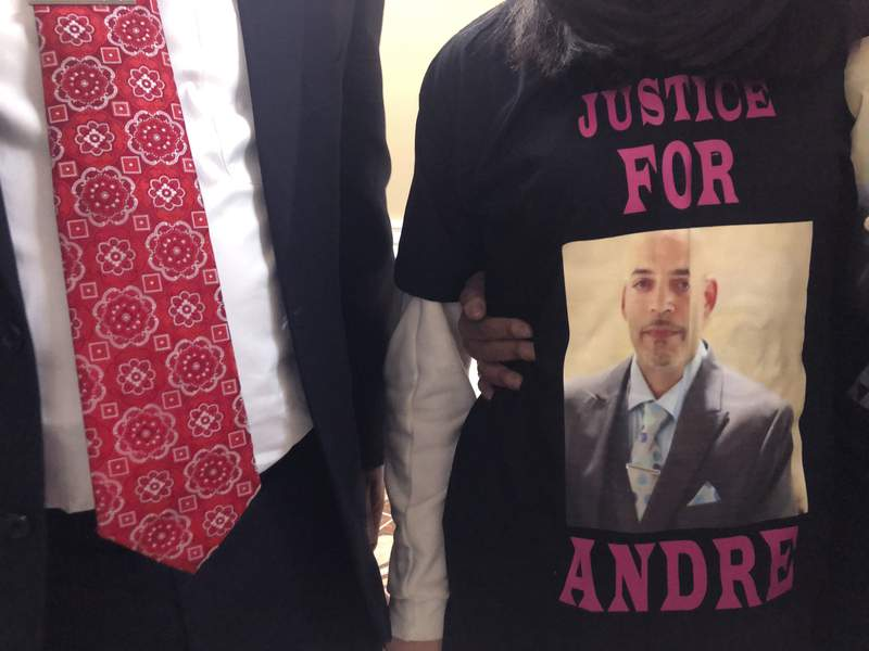 FILE - Andre Hill, fatally shot by Columbus police on Dec. 22, is memorialized on a shirt worn by his daughter, Karissa Hill, on Thursday, Dec. 31, 2020, in Columbus, Ohio.  Ohios capital city will pay a $10 million settlement for the family of Hill, a Black man who was fatally shot by a white Columbus police officer in December as he emerged from a garage holding a cellphone, the Columbus city attorney announced Friday, May 14, 2021.  (AP Photo/Andrew Welsh-Huggins, File)