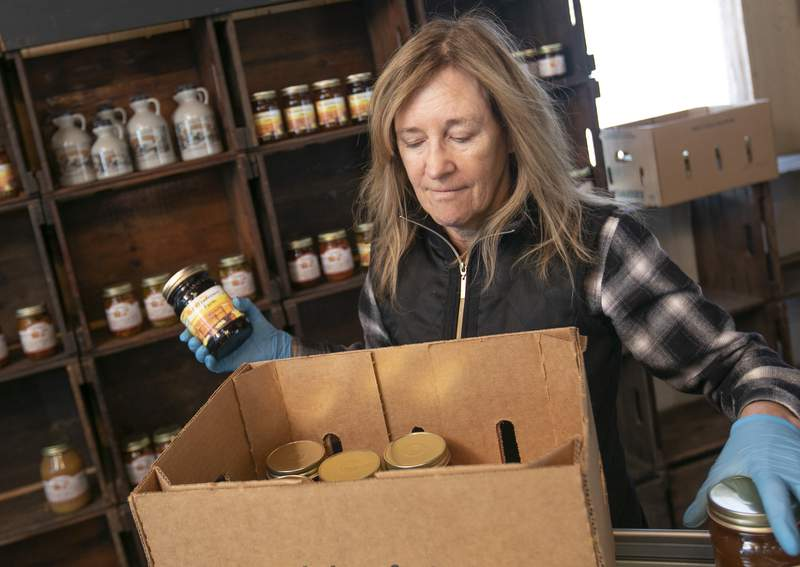 """Linda DeFrancesco stocks shelves with her farm's own salsa, spreads, veggies and salsa at DeFrancesco Farm Stand in Northford, Conn., Thursday, March 26, 2020. Businesses across the state are worried about the impact of the coronavirus, even the ones considered """"essential"""" like farmers' markets and garden centers. The farm stand opens Saturday at 10 a.m. (Dave Zajac/Record-Journal via AP)"""