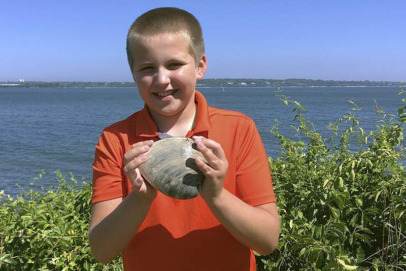 In this Tuesday, July, 28, 2020, photo provided by the University of Rhode Island, Cooper Monaco holds the large quahog he found Monday while clamming with his grandfather in Westerly, R.I. The quahog is more than five inches across and weighing more than two pounds, and is among the largest ever harvested in the state. The mollusk was donated to the University of Rhode Island's Marine Science Research Facility. (Todd McLeish/University of Rhode Island via AP)