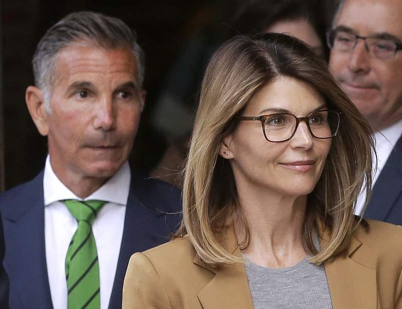 """FILE - In this April 3, 2019, file photo, actress Lori Loughlin, front, and her husband, clothing designer Mossimo Giannulli, left, depart federal court in Boston. """"Full House"""" actress Loughlin, Giannulli and other prominent parents told a judge Wednesday, March 25, 2020, that he should dismiss charges against them in the college admissions bribery case, accusing prosecutors of """"extraordinary"""" misconduct. (AP Photo/Steven Senne, File)"""