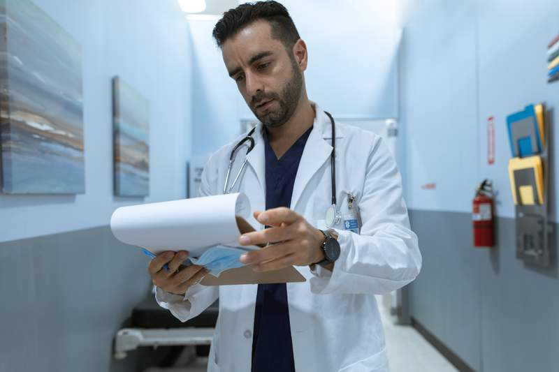 A doctor looks at a clipboard.