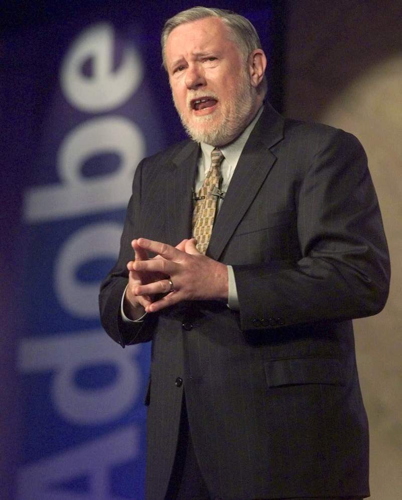 """FILE - In this June 24, 1999, file photo, Dr. Charles M. Geschke, president, co-chairman and co-founder of Adobe Systems Inc., delivers his keynote address about the future of workplace information on the final day of PC Expo at New York's Jacob K. Javits Convention Center. Charles """"Chuck"""" Geschke, the co-founder of the major software company Adobe Inc., who helped develop Portable Document Format technology, or PDFs, died at age 81. Geschke, who lived in the San Francisco Bay Area suburb of Los Altos, died Friday, April 16, 2021, the company said. (AP Photo/Richard Drew, File)"""