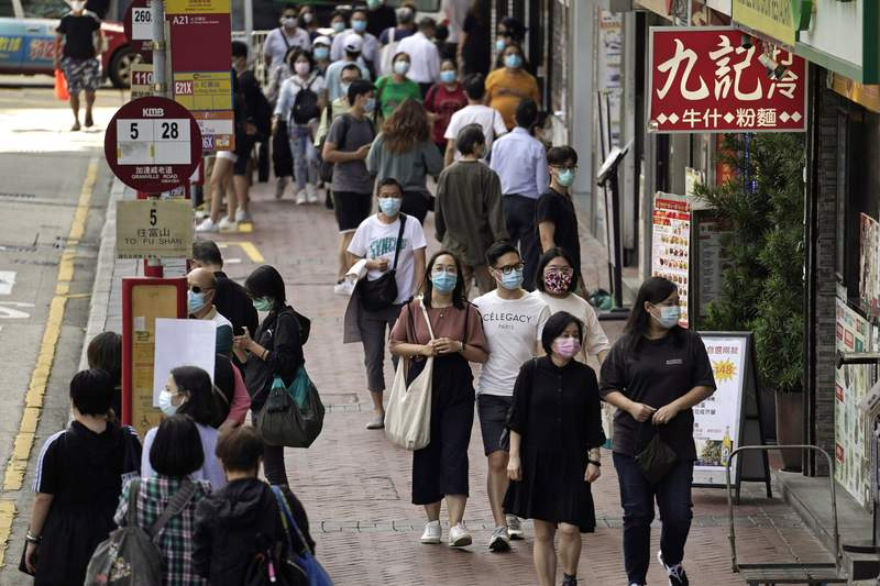 FILE - In this Oct. 9, 2020, file photo, people wearing masks to protect against the coronavirus, walk down a street in Hong Kong. Singapore and Hong Kong have postponed a planned air travel bubble meant to boost tourism for both cities, amid a spike in coronavirus infections in Hong Kong. The air travel bubble, originally slated to begin Sunday, will be delayed by at least two weeks, Hong Kongs minister of commerce and economic development, Edward Yau, said at a news conference on Saturday, Nov. 21, 2020. (AP Photo/Kin Cheung, File)