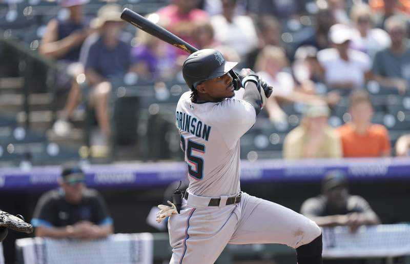 Miami Marlins' Lewis Brinson follows the flight of his double that drove in two runs off Colorado Rockies starting pitcher Kyle Freeland in the fifth inning of a baseball game Sunday, Aug. 8, 2021, in Denver. (AP Photo/David Zalubowski)