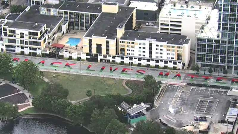 Crews painting Black Lives Matter street mural in downtown Orlando