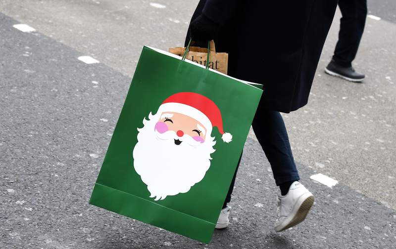 A person carries a Christmas themed shopping bag as non-essential shops are allowed to reopen after England's second lockdown ended at midnight, in Oxford Street, in London, Wednesday, Dec. 2, 2020. Pfizer and BioNTech say they've won permission Wednesday for emergency use of their COVID-19 vaccine in Britain, the world's first coronavirus shot that's backed by rigorous science -- and a major step toward eventually ending the pandemic. (AP Photo/Alberto Pezzali)