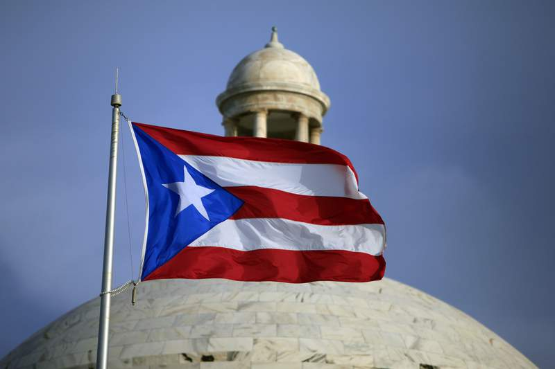FILE - In this July 29, 2015 file photo, the Puerto Rican flag flies in front of Puerto Rico's Capitol as in San Juan, Puerto Rico. A federal control board that oversees Puerto Ricos finances submitted a proposed $10 billion budget on Thursday, June 11, 2020, as federal legislators debate whether to curtail the boards power over the U.S. territory. (AP Photo/Ricardo Arduengo, File)