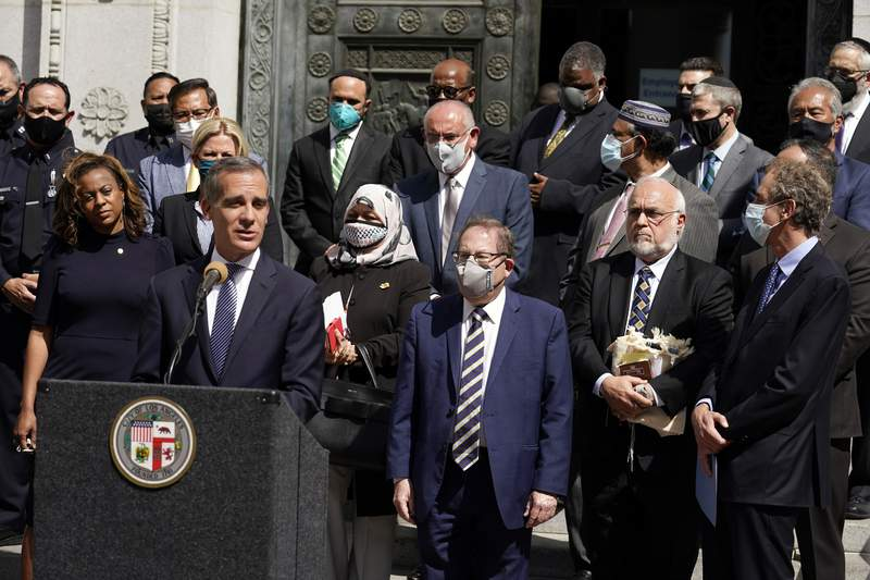 FILE - In this Thursday, May 20, 2021, file photo, Los Angeles Mayor Eric Garcetti, at podium, speaks in front of civic and faith leaders outside City Hall in Los Angeles. Faith and community leaders in Los Angeles called for peace, tolerance and unity in the wake of violence in the city that is being investigated as potential hate crimes. Los Angeles police on Saturday, May 22, 2021 announced the arrest of a suspect in an alleged attack by a pro-Palestinian group on Jewish men outside a restaurant earlier in the week. (AP Photo/Marcio Jose Sanchez, File)